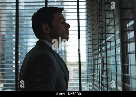 Businessman looking through the window - Stock Photo