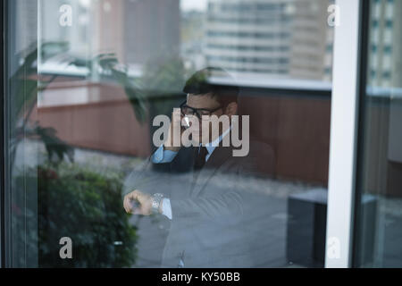 Businessman talking on phone while checking time - Stock Photo
