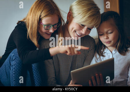 Mother and her kids using digital tablet at home - Stock Photo