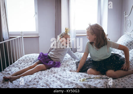 Sisters in costume having  fun on bed - Stock Photo