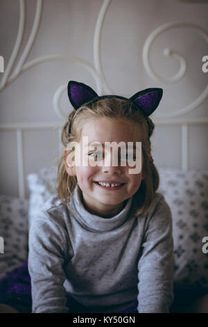Portrait of smiling girl sitting on bed - Stock Photo