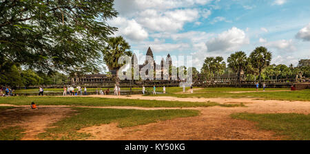 Panorama of the main Buddhist temple complex of 12th century Angkor Wat with tourists in the foreground at Siem - Stock Photo