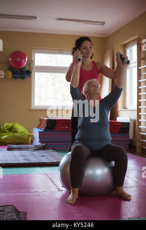 Female therapist assisting senior woman with dumbbells and exercise ball - Stock Photo