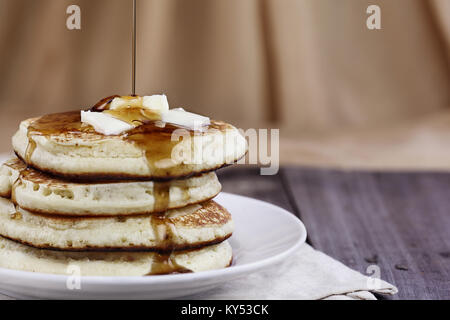 Stack of homemade pancakes with melting butter and syrup being poured onto them. Extreme shallow depth of field. - Stock Photo