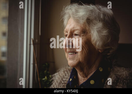 Smiling senior woman looking out of the window - Stock Photo