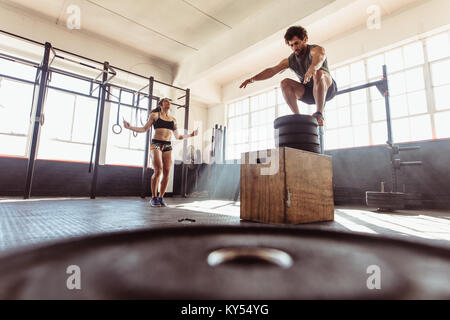 Fit young man box jumping with woman exercising with skipping ropes at a cross training style gym. Couple during - Stock Photo