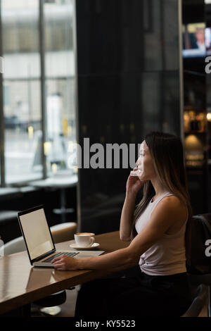Businesswoman talking on phone while working on laptop - Stock Photo