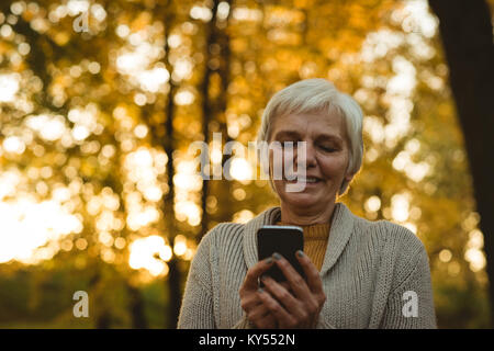 Smiling senior woman using a smart phone in a park - Stock Photo