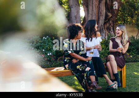 Cheerful young women hanging out with drinks. Group of female friends sitting outdoors and having fun. - Stock Photo