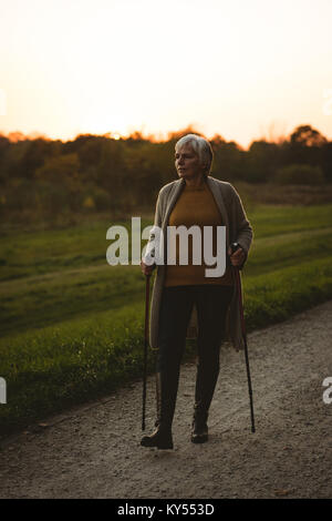 Senior woman walking on a dusty road with walking sticks - Stock Photo