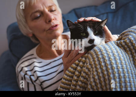 Senior woman sitting on sofa while stroking her cat at home - Stock Photo