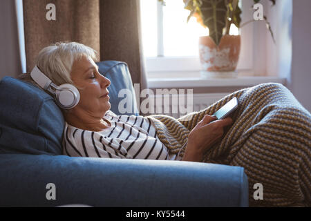 Senior woman listing to music on phone while siting on sofa in living room - Stock Photo