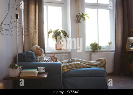 Senior woman relaxing on sofa in living room at home - Stock Photo