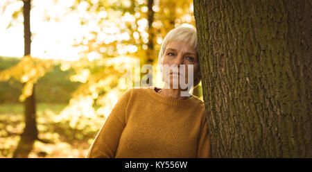 Thoughtful senior woman leaning on tree trunk in the park - Stock Photo