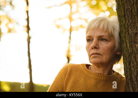 Thoughtful senior woman leaning on tree trunk in the park on a sunny day