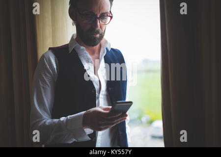 Businessman using mobile phone near window - Stock Photo