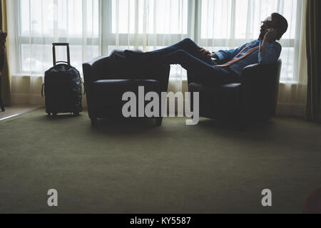 Businessman talking on mobile phone while leaning on arm chair - Stock Photo