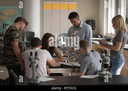 Teacher assisting students in experiment on molecule - Stock Photo