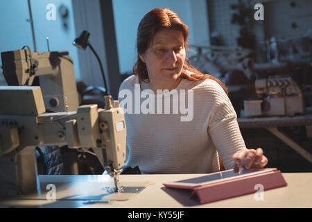 Tailor using digital tablet - Stock Photo