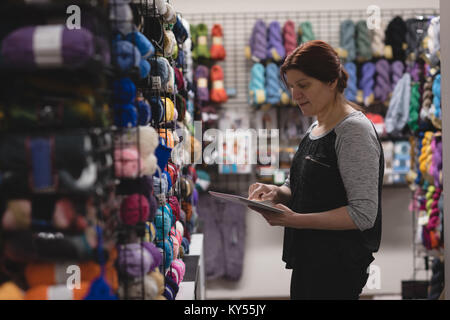 Woman using digital tablet in tailor shop - Stock Photo