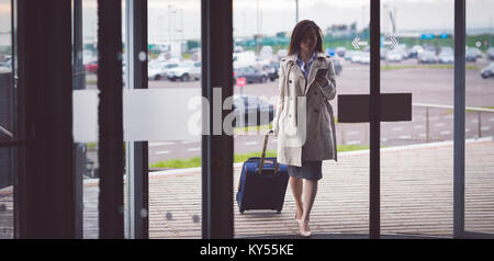 Businesswoman using mobile phone while arriving in hotel - Stock Photo