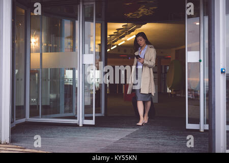 Businesswoman using mobile phone while walking out of the hotel - Stock Photo