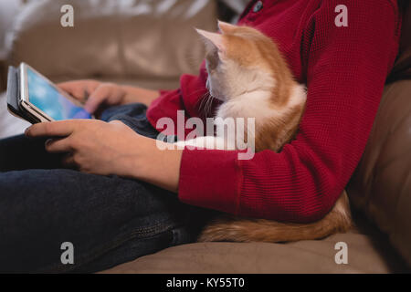 Boy using digital tablet in living room with his cat - Stock Photo
