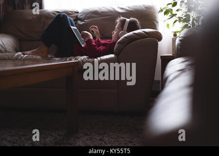 Boy using digital tablet with headphones in living room - Stock Photo