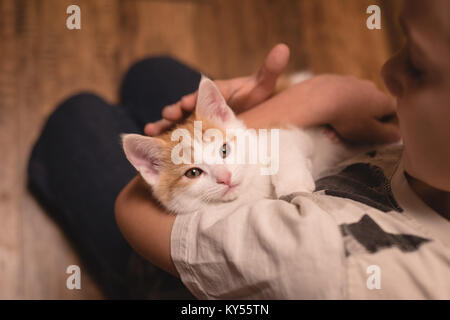 Boy holding her cat in living room - Stock Photo