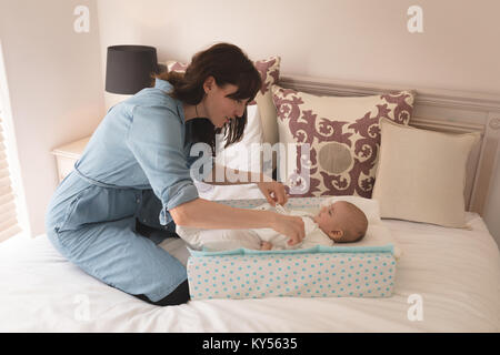Cute little baby getting dressed by her mother on bed in the bedroom