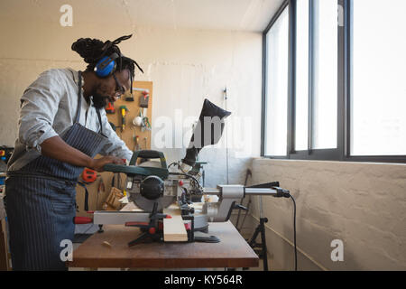 Carpenter cutting wooden plank with electric saw - Stock Photo