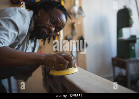 Carpenter leveling wood with work tool - Stock Photo