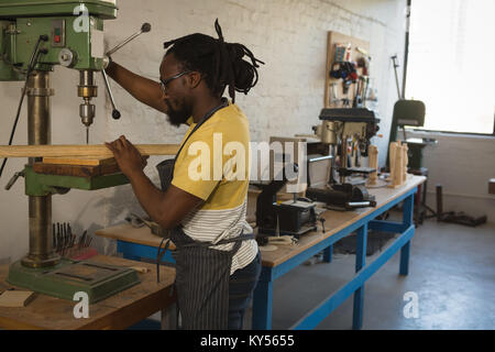 Carpenter drilling wooden plank with machine - Stock Photo