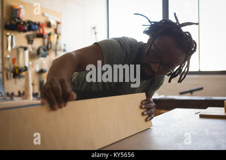 Carpenter looking at wooden plank - Stock Photo