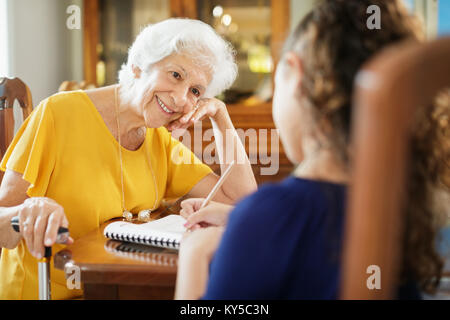 Happy little girl doing school homework with elderly woman at home. Family relationship with grandmother and granddaughter. - Stock Photo