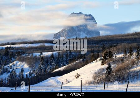 Chief mountain surrounded by a bed of low lying clouds and a fresh snow fall that covers the valley below - Stock Photo