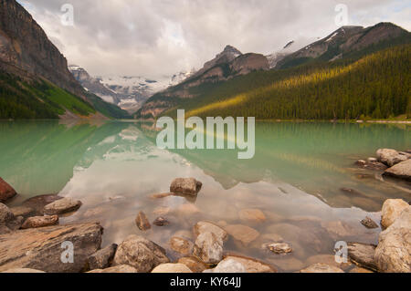 First rays of golden sunlight on the mountains at Lake Louise with peaceful reflections. - Stock Photo
