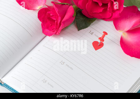 Calendar Valentines day pink pin and red roses on calendar notebook. love appointment concept - Stock Photo