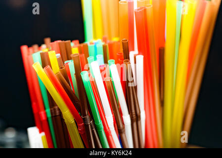 colored cocktail tubes standing in a glass top view, Drinking straws - Stock Photo