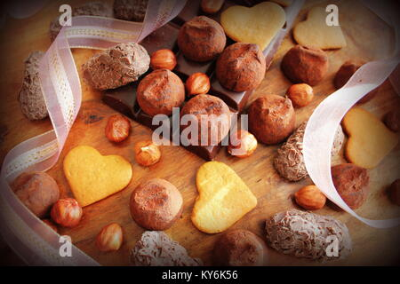 Gourmet chocolate truffles and cookies for Valentine's Day. Chocolate candy served with decorative ribbon - Stock Photo