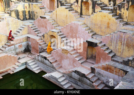 Two local women in traditional dress walking at the stepwell Panna Meena Ka Kund, Jaipur, Rajasthan, India. - Stock Photo