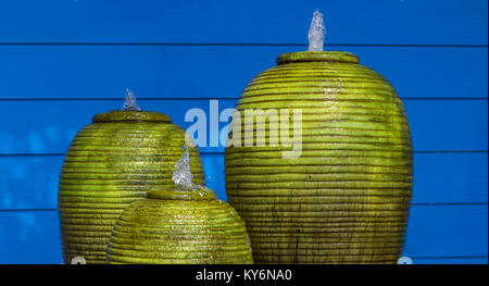 Green fountain jar and blue walls peaceful. - Stock Photo