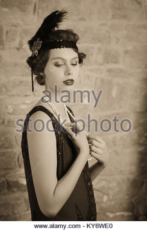 Portrait of a woman in a 1920's vintage style flapper dress shot in black and white and sepia toned. - Stock Photo