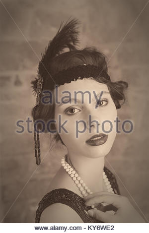 Head and shoulders portrait shot of a woman in a 1920's vin gate flapper hat shot in black and white with sepia - Stock Photo