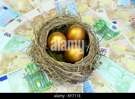 Golden eggs in a nest laying on a bed of money. - Stock Photo