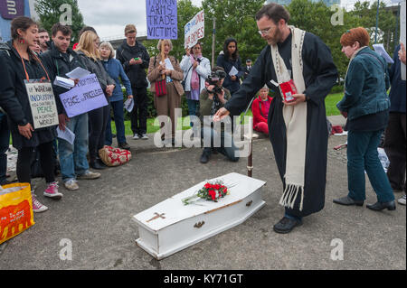 The priest sprinkles incense on the coffin at the end of the mock funeral by London Catholic Workers for victims - Stock Photo