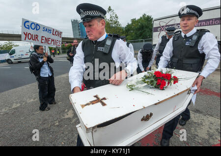 Police carry the coffin placed on the road by London Catholic Workers for their mock funeral for victims of the - Stock Photo