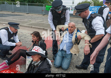 Some protesters who refuse to move are lifted up by police and carried to the pavement as they clear the road after - Stock Photo