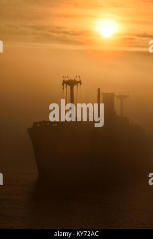 Beautiful sunrise haze  with a greek shipwreck Evangelia on the shore of Black Sea near Costinesti, Romania. - Stock Photo