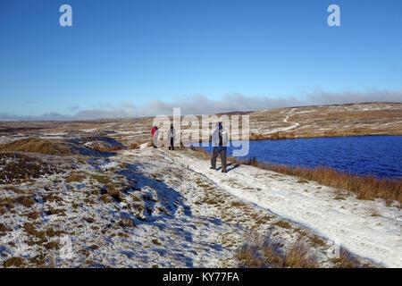 Three Hikers Walking Past Coalgrovebeck Reservoir near Grassington Moors Disused Lead Mines in Winter, Yorkshire - Stock Photo